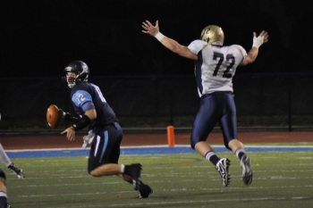 Quarterback Robert Meade evades a TCNJ defender Photo Credit: Carl Stoffers