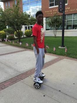 William Asante riding his hover board down Cougar Walk.